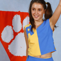 Sweet pigtailed brunette cheerleader Benta cheering and stripping